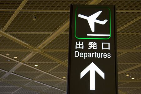 An airport departure sign in English and Japanese