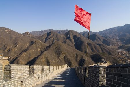 View of the Great Wall of China with red flag and blue sky Stock Photo