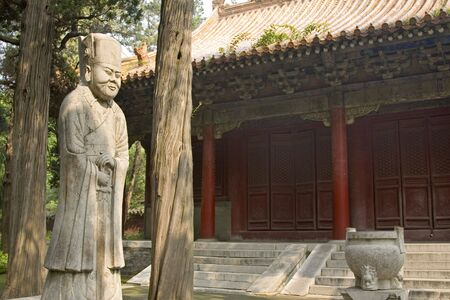 An ancient statue of Confucius beside a temple