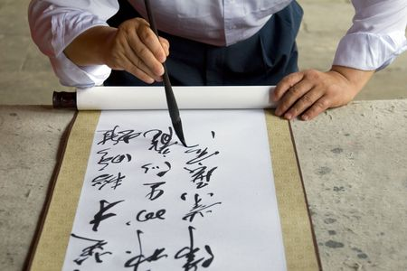 A Chinese calligrapher at work writing on a scroll