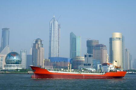 A bright red ship with the Shanghai skyline in the background Stock Photo