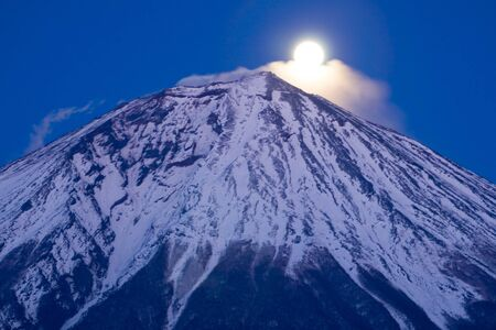 The Moon rising over the peak of Mt. Fuji at dusk
