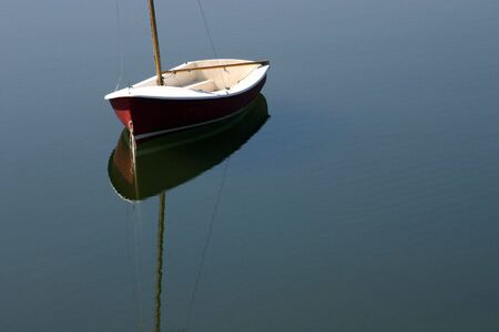 dingy: A small sailboat and its reflections Stock Photo