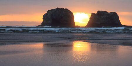 Beautiful panorama shot of two large rocks on the Oregon coast at sunset  photo