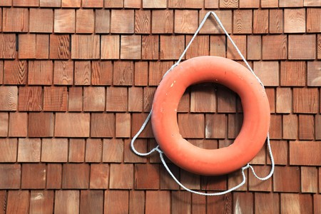 cedar shakes: An orange lifesaver hanging on a wooden boathouse Stock Photo