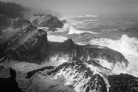 A dramatic black and white view of the Oregon Coast during stormy weather Stock Photo