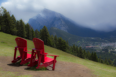 Two red chairs overlooking the town of Banff, Alberta