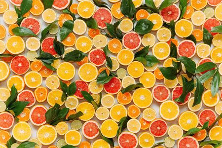 a wall of apricots, grapefruits and tangerines is decorated with leaves; background texture