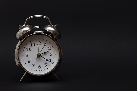 vintage alarm clock on black background.For time concept.