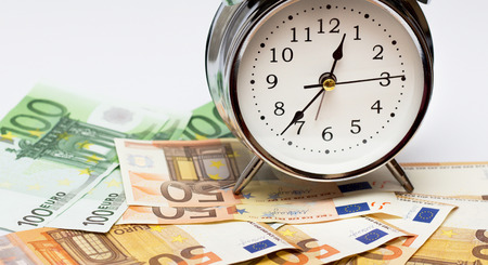 An alarm clock, and European paper money, on a white background. Business concept, time is money. 免版税图像