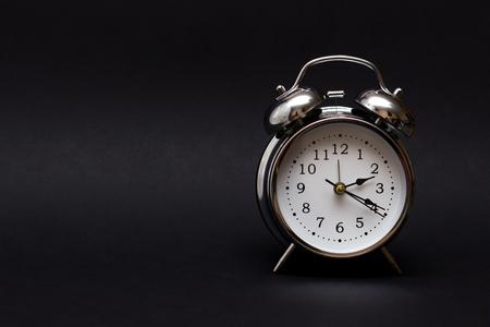 Reloj despertador vintage sobre fondo negro. Por concepto de tiempo. Foto de archivo