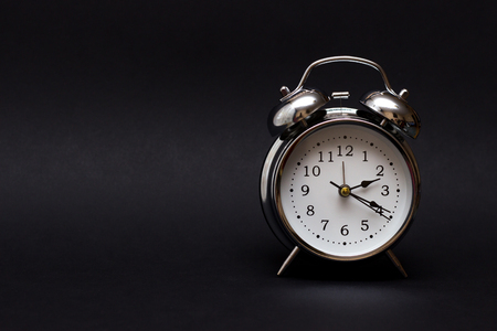 vintage alarm clock on black background.For time concept.
