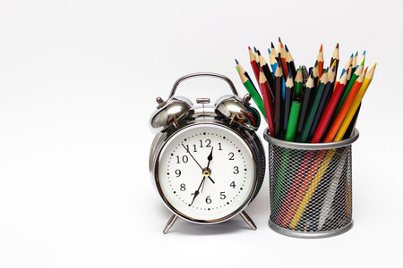 Alarm clock, colored pencils in a metal glass. The concept of time, and the business concept.