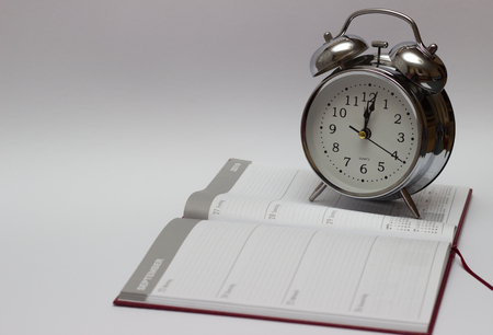 alarm clock and diary on a white background. For time concept. 免版税图像