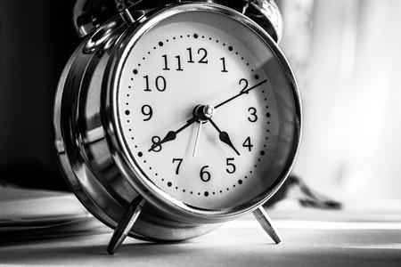 Black vintage alarm clock on black background.