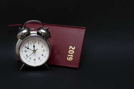 Alarm clock and notebook on black background, For time concept.