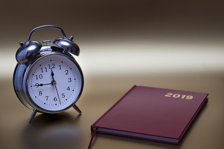 Alarm clock and notebook on gold background, For time concept.