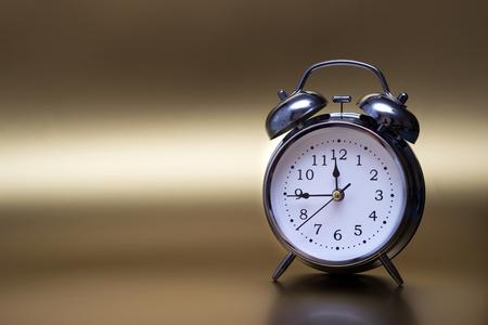 vintage alarm clock on gold background. For time concept.