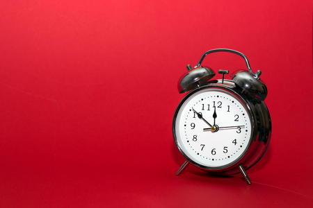 red alarm clock on red background. close up shot. top view. For time concept.