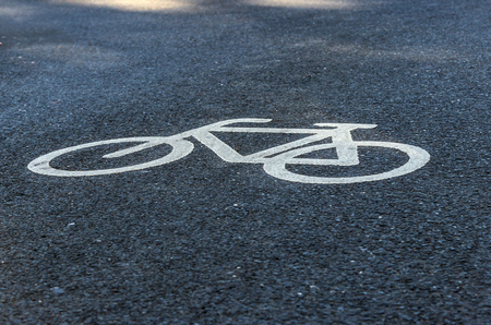 Close up view of a cyclist painted in white on an asphalt cycle track. Traffic sign to indicate a bike path in a town. 免版税图像