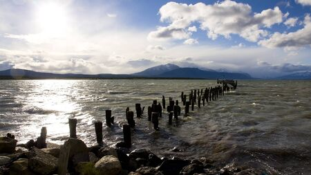 The historical remains of the pier on a lake in Puerto Natales