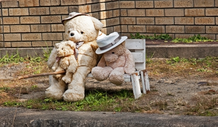 Family of teddy bears sitting on a bench and catching fish