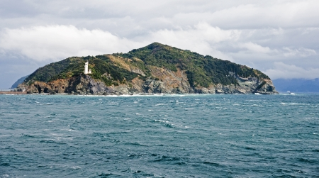 White lighthouse on a small green island in Japan Stock Photo