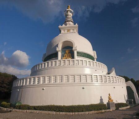 Golden Buddha and big white stupa in Beppu, Japan
