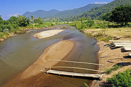 The construction of bamboo rafts on the river bank in Pai