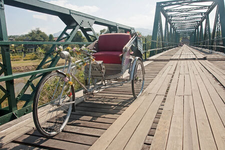 antique tricycle: Tricycle on old bridge - memorial bridge in Pai  Thailand  Stock Photo
