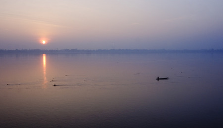 Boat on the Mekong River at sunset - Laos photo