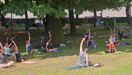 KATOWICE, POLAND - JULY 19, 2015: People who practice yoga in the park on 19 July 2015 in Katowice, Poland. In the center of Katowice in the park you can meet people practicing yoga Publikacyjne