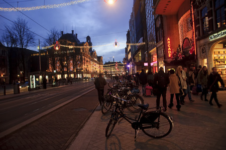 5 december: AMSTERDAM, NETHERLANDS - DECEMBER 5, 2015: The main street of the town on 5 December 2015 in Amsterdam, Netherlands. During the Christmas period the streets are decorated with colorful lights. Editorial