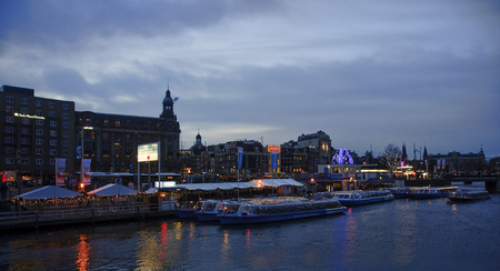 '5 december': AMSTERDAM, NETHERLANDS - DECEMBER 5, 2015: Boats on the canal in front of the railway station on 5 December 2015 in Amsterdam, Netherlands. Boat launch during the holiday season is decorated with colorful lights. Editorial