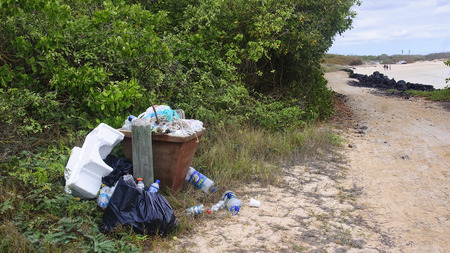 not full: PUERTO VILLAMIL, ECUADOR - NOVEMBER 19, 2015: Trasch full of rubbish on the beach on 19 November 2015 in Puerto Villamil, Ecuador.The beaches of the Galapagos islands are frequented not only by tourists Editorial