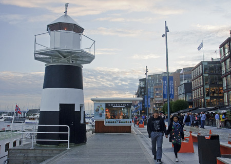 OSLO, NORWAY - SEPTEMBER 16, 2016: Aker Brygge in Oslo and lighthouse on 16 September 2016 in Oslo, Norway. It is a very popular place for walks in the city center