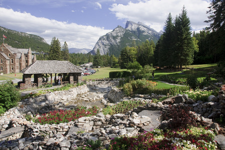 frequented: BANFF, CANADA - SEPTEMBER 1, 2016: Parks Canada Administration Building in Cascade Garden on 1 September 2016 in Banff, Canada. This place is situated in the center of the city and is frequented by tourists