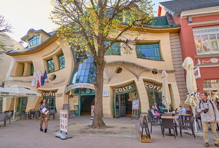 SOPOT, POLAND - APRIL 29, 2018: Crooked little house (Krzywy Domek) on 29 April 2018 in Sopot, Poland. The Crooked House is an irregularly-shaped building. 1 of 50 strangest buildings of the world.