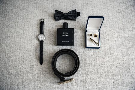 There are various mens accessories on the table, such as cufflinks, watches, straps, butterflies, and cologne. 스톡 콘텐츠