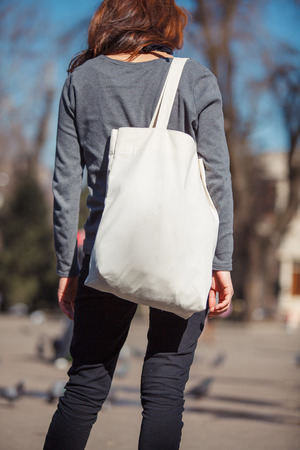 Girl with bag over his shoulder outdoors Reklamní fotografie - 72392797