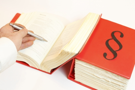 seeking in law book wth pen in Hand Stock Photo