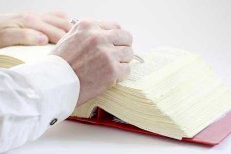 hand met pen zoekt in boek Stockfoto