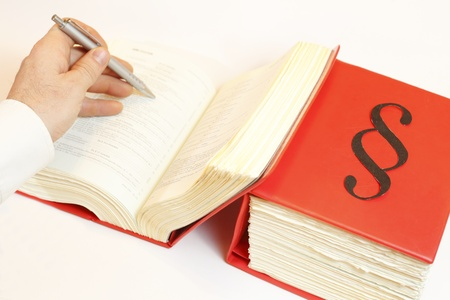seeking in law book wth pen in Hand Stock Photo
