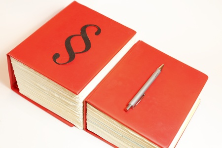 red books with pen laying on board Stock Photo