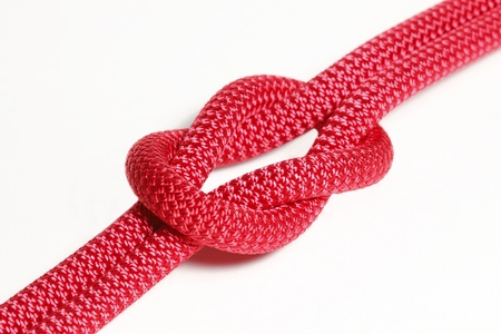 rood touw met een knoop op een witte achtergrond Stockfoto