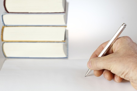 hand with pen on table with book stack on background photo