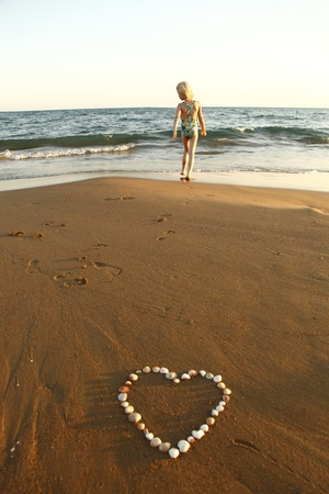 heartache: mussels heart at coast with young girl in background Stock Photo