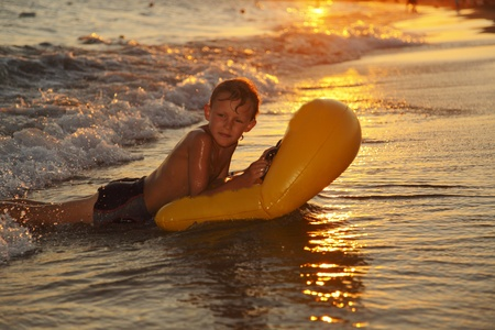 a boy is surfing on the beach at afternoon