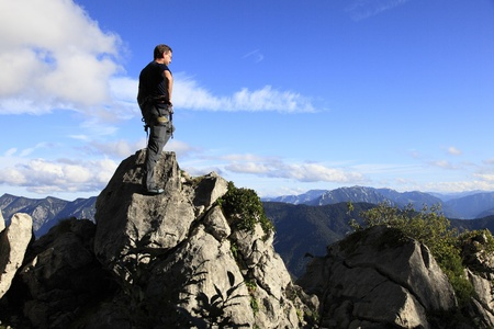 climber is standing on top of a mountain Stock Photo