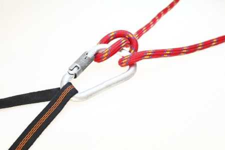 rapelling: red rope and carabiner with knot for climbing